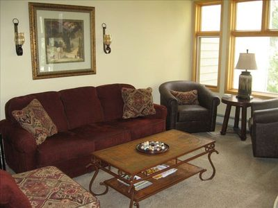 Spacious living area with lots of windows and light and cozy wood burning stove.