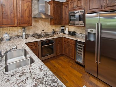 Fully equipped gourmet kitchen with high end appliances including a wine fridge