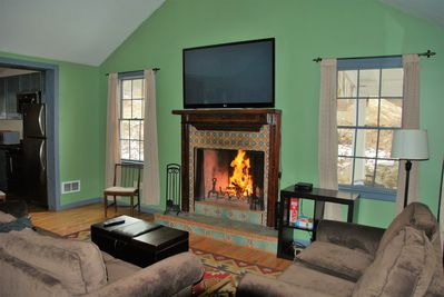 "Wood fireplace and 60"" flatscreen TV in the living room"