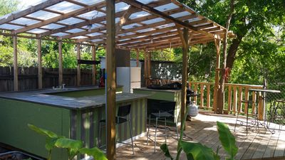 Outdoor kitchen has sink refrigerator ,microwave , bar seating, griddle