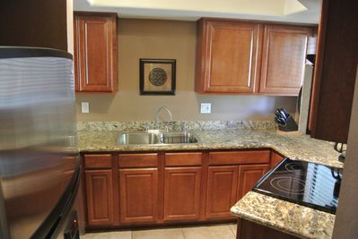 Kitchen with granite slab counters and stainless appliances.