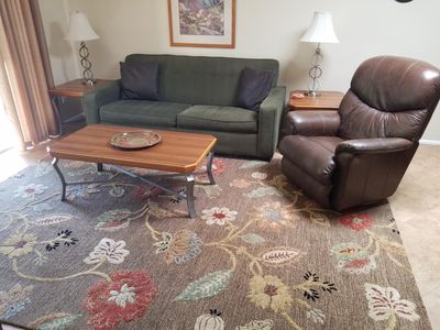 sleeper sofa and recliner brown leather chair in living room.
