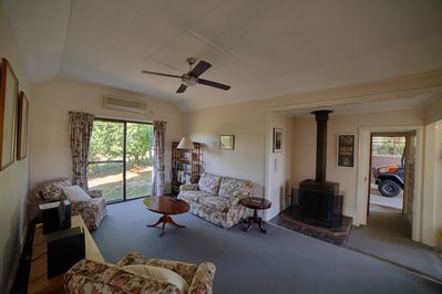 Living Room with wood fire. Door to carport