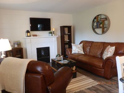 Comfortable living space with fireplace, leather couch and chair with ottaman.