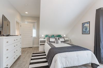 Bedroom has a queen bed, private balcony, and smart TV