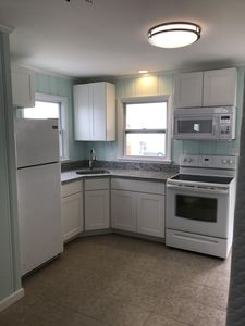 The new kitchen has granite counter tops, tile floors, basic cooking supplies