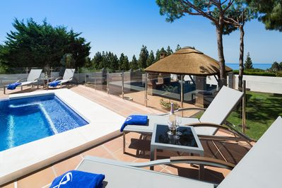 pool area with thatched gazebo all with sea views.