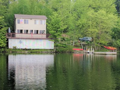 Lake front home with two kayaks, a canoe, private swim raft, and a dock.