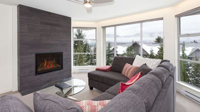 Spacious and bright living area with fireplace, mountain views and large screen TV.