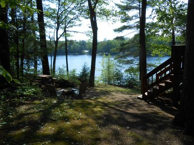 Left side of cottage w/ fire pit, picnic table, private water front.