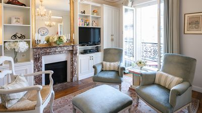 The living area features a beautiful large mirror and classic French windows