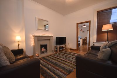 Comfortable living room; wood effect flooring, gas fire, comfy 2&3 seater sofas
