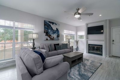 Large flat screen smart TV above fireplace and lots of windows offer great natural lighting