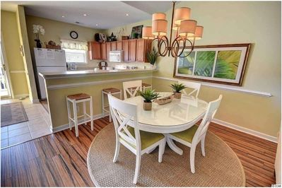 Open concept kitchen with breakfast bar and dining table, seating for 8.
