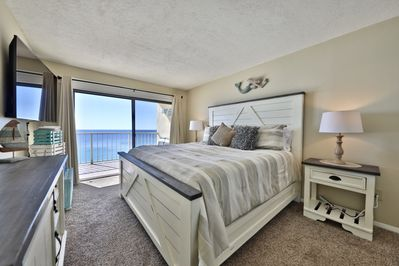 Master bedroom with king sized bed and access to balcony