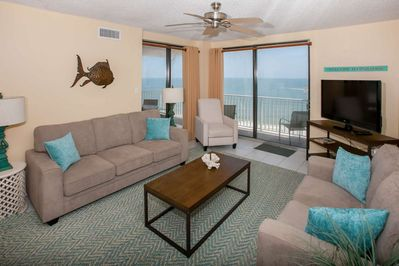 """Living room w/seating for 6, a 55"""" TV and access to the Gulf-front balcony"""