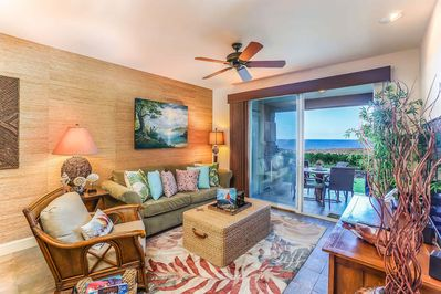 Modern chic living room with seating, Hawaiian inspired decor, and sliding glass door to lanai