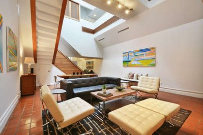 Main living room with 2 story high ceiling and skylights.