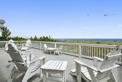 Large oceanfront deck with Adirondack chairs overlooks a beautiful dune  & beach