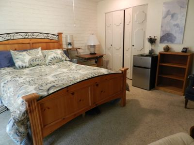 bed, refrigerator, computer desk with chair and 2 lamps and walk-in closet