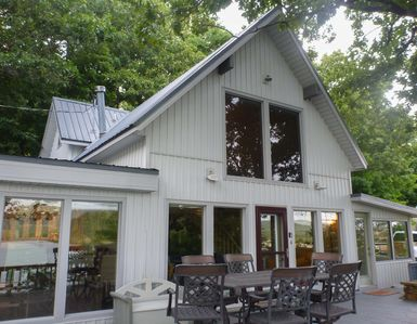 Sunrise Cottage boasts incredible amenities with a wall of windows toward lake