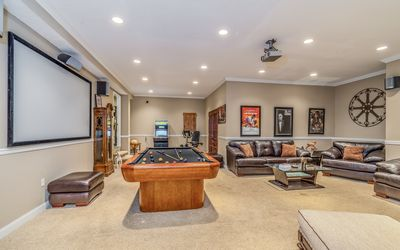 Game Room - The sunken game room has posh seating, a pool table, and a theater projector system.