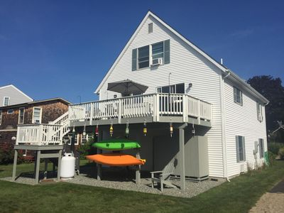 Back of house with large deck, outside shower, lawn and kayaks