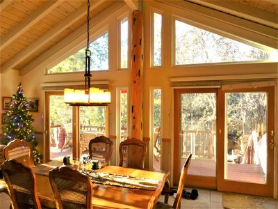 Vaulted wood ceiling dining room with Christmas Tree and back deck tree view...