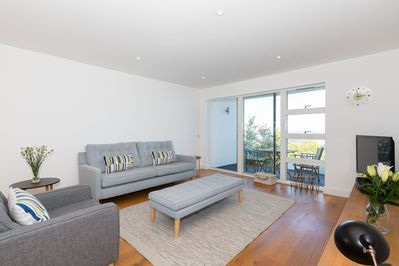 Spacious living room with direct ocean views to Godrevy Lighthouse and beyond