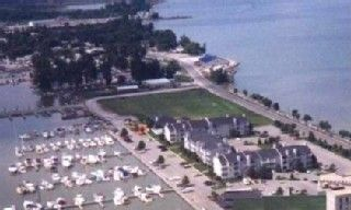 Aerial view of condo complex with lake and marina