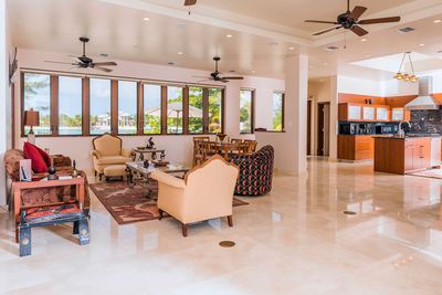 The living room features multiple seats and stunning views.