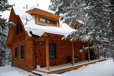 Newly constructed log home with covered front porch and rockers