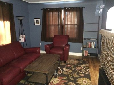 Living room with leather couch/chair.  Books and DVDs.