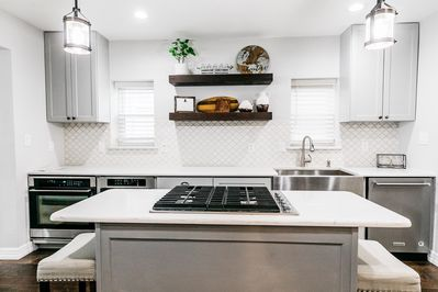 Gas cooktop in island with pull-out trash cans and auto on kitchen faucet.