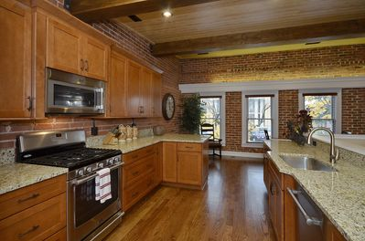 Well stocked, beautifully updated kitchen features upgraded appliances & granit