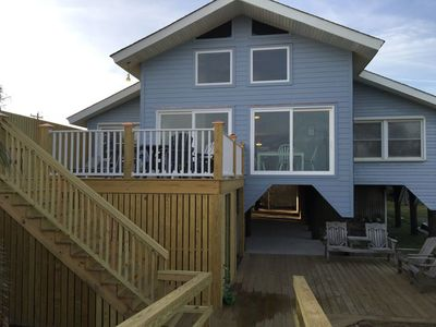 Oceanside of house with large windows. Upper and lower deck