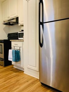 The kitchen has stainless steel appliances - fridge, dishwasher, stove/oven.