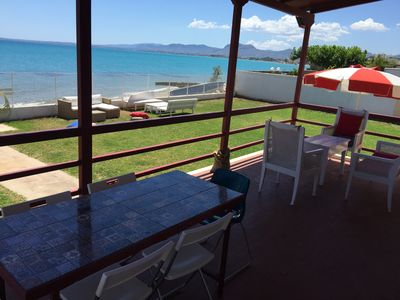 Veranda dining table and lounge with garden and sea view.