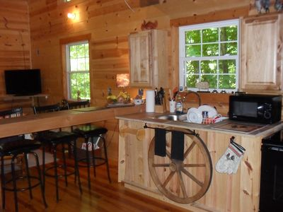 view of kitchen with stone counter tops and bar, ponderosa pine interior.