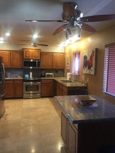 Kitchen with travertine flooring and stainless appliances.