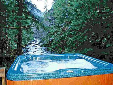 Large hot tub at edge of view deck overlooking river and forested mountains