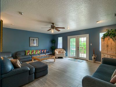 The large living room has french doors that open out to the deck. 2 sofas, TV