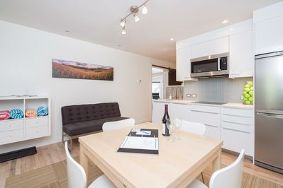 The kitchen has a small dining table for 4 people and a small loveseat sofa.