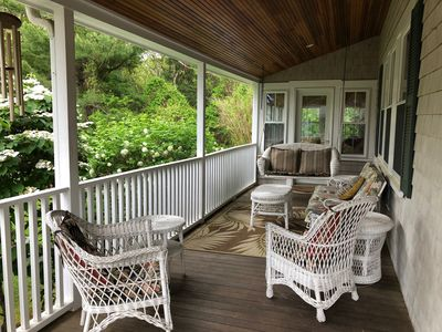 Side porch with wicker furniture for those relaxing moments.