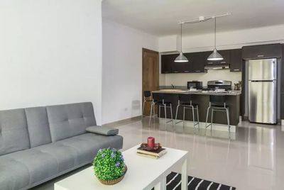 The livingroom comes with an open fully equipped kitchen, balcony, seating area,