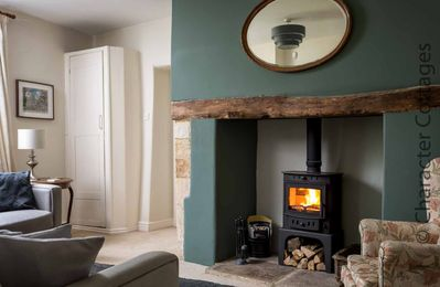 The lovely living room contains a large fireplace with a cosy wood burning stove