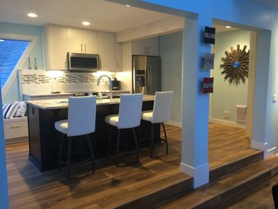 Bright kitchen with quartz island and brand new stainless steel appliances.