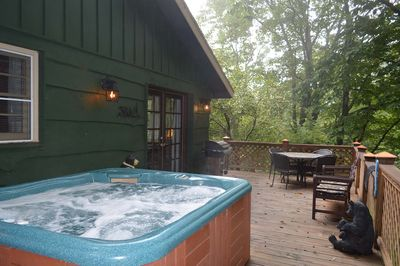 Back deck with hot tub, table, chairs and a grill