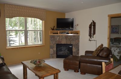 """cozy, bright living room with gas fireplace and 40"""" HDTV"""