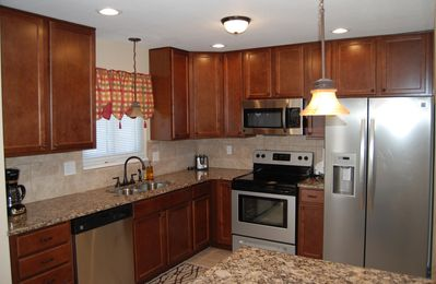 Updated kitchen with granite counters, tile backsplash, and steel appliances